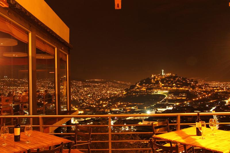 Vista exterior nocturna al panecillo, botella de vino | Restaurante El Ventanal